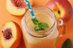 Smoothies made from ripe peaches in a glass jar royalty free stock images