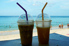 Smoothies of mango and passion fruit on the beach Royalty Free Stock Photos