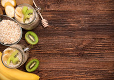 Smoothies with oatmeal, banana, kiwi in glass jars on a wooden background. Stock Photo