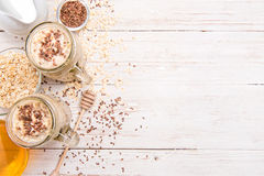 Smoothies with oatmeal, flax seeds in glass jars on a wooden background. Stock Photos