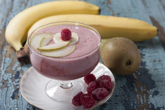 Smoothies of pear, banana and frozen raspberries with yogurt. Bananas and pears in the background on an old blue table Stock Image