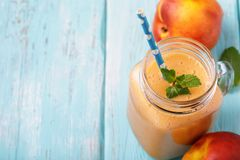 Smoothies prepared from ripe peaches in a glass jar royalty free stock image