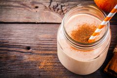 Smoothies with red apple and cinnamon in a glass mason jar. Healthy breakfast: smoothies with red apple and cinnamon in a glass mason jar on a wooden background Stock Photography