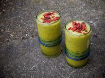 Smoothies with red goji berries on top. Green healthy drink for longer life Stock Photography