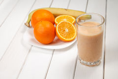 Smoothies sains d'orange et de banane de boissons sur la table en bois Image libre de droits