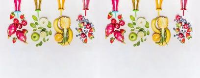 Smoothies sanos diversos de las frutas con los ingredientes coloridos en el fondo de madera blanco, visión superior, bandera Fotos de archivo