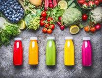 Smoothies sanos y jugos rojos, anaranjados, verdes, amarillos y rosados en botellas en fondo concreto gris con vegeta orgánico fr Imagen de archivo