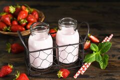Smoothies with strawberries and yogurt in jars on a wooden background. Detox menu. Smoothies with strawberries and yogurt in jars on a wooden background