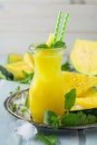 Smoothies van gele watermeloen met ijs en muntbladeren in een glas Stock Afbeelding