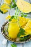 Smoothies van gele watermeloen met ijs en muntbladeren in een glas Royalty-vrije Stock Foto's