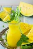 Smoothies van gele watermeloen met ijs en muntbladeren in een glas Stock Fotografie