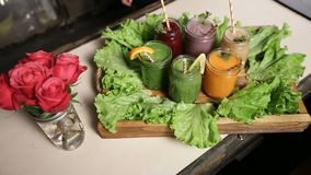 Smoothies of various colors and tastes in jars. Freshly blended smoothies of various colors and tastes in jars served on wooden tray decorated by green salad stock footage