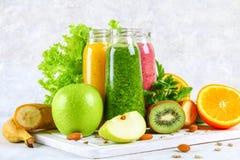Smoothies verdes, amarillos, púrpuras en las botellas de la pasa, perejil, app Fotos de archivo