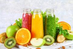 Smoothies verdes, amarillos, púrpuras en las botellas de la pasa, perejil, app Imagen de archivo
