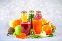 Smoothies verdes, amarillos, púrpuras en las botellas de la pasa, perejil, app Fotografía de archivo