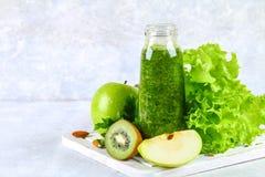 Smoothies verdes del perejil, ensalada, kiwi, manzana en una botella encendido Fotografía de archivo libre de regalías
