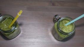 Smoothies verts dans des pots de maçon avec des tubes sur une table en bois banque de vidéos