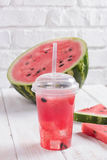 Smoothies Of Watermelon Juice In A Plastic Cup With A Straw. Fre. Smoothies Of Watermelon Juice In Plastic Cup With Straw. Fresh Red Drink With Ice On The White Stock Photography
