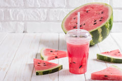 Smoothies Of Watermelon Juice In A Plastic Cup With A Straw. Fresh Red Drink With Ice On The White Background Of Wooden Planks. C. Smoothies Of Watermelon Juice stock images