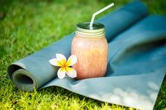 Smoothies y estera de la yoga en la hierba Foto de archivo