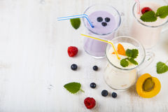 Smoothies or yogurt with fresh berries. Milkshakes with raspberries, blueberries, apricots and mint leaves. Smoothies or yogurt with fresh berries on a wooden royalty free stock images