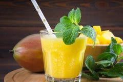 Smoothiesmango med sugrör och mintkaramellen i en glass dryckeskärl Platta med den skivade mango En tropisk frukt spelrum med lam Arkivfoton