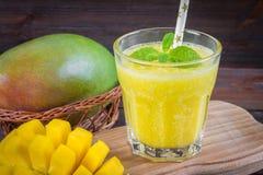 Smoothiesmango med sugrör och mintkaramellen i en glass dryckeskärl Platta med den skivade mango En tropisk frukt spelrum med lam Fotografering för Bildbyråer