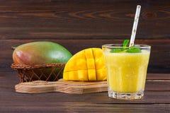 Smoothiesmango med sugrör och mintkaramellen i en glass dryckeskärl Platta med den skivade mango En tropisk frukt spelrum med lam Arkivfoto