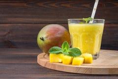 Smoothiesmango med sugrör och mintkaramellen i en glass dryckeskärl Platta med den skivade mango En tropisk frukt spelrum med lam Arkivbilder
