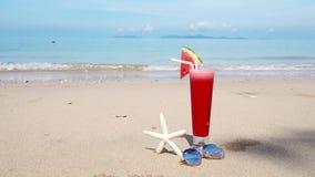 Smoothiewassermelonensaft und -Sonnenbrille auf Sommerstrandhintergrund stock video