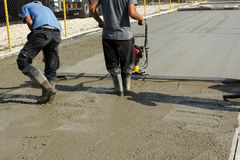 Smoothing concrete with vibrating screed machine. Workers on a construction site smoothing freshly poured concrete with a gas powered vibrating screed machine Stock Photo
