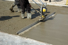 Free Smoothing Concrete With Gas Powered Vibrating Screed Machine Royalty Free Stock Image - 80144996
