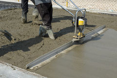 Smoothing fresh concrete with gas powered vibrating screed machine. On a construction site Royalty Free Stock Photos