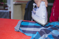 Smoothing-iron. Ironing a shirt on an ironing board Royalty Free Stock Photos