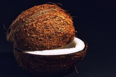 Smoothly cut halves of coconut. Two halves of the coconut are evenly cut lying on a black background Stock Photo