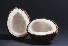 Smoothly cut halves of coconut. Two halves of the coconut are evenly cut lying on a black background Stock Images