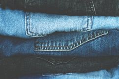 Smoothly folded pile of denim pants. Fashion clothes stock photos