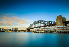Smoothly sea by long exposure shot with Harbor bridge Royalty Free Stock Image