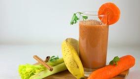 Smoothy orange dans un verre Banane, carotte, persil et céleri vidéo du chariot 4K banque de vidéos