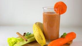 Smoothy orange de versement dans un verre Banane, carotte, persil et céleri vidéo 4K clips vidéos