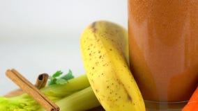 Smoothy orange en verre Banane, carotte, persil, céleri macro vidéo du chariot 4K banque de vidéos