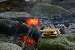 Smore Beside a Campfire. A smore, made of chocolate, marshmallow, and graham cracker sitting on a rock beside the campfire Stock Photography