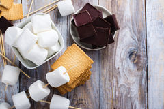 Smores dessert ingredients. On wooden table. Picnic or camp concept. Space for text stock images
