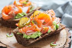 Smorrebrod with salmon on rye bread with vegetables and herbs. Danish open sandwich Smorrebrod with salmon on rye bread with vegetables and herbs Stock Photography