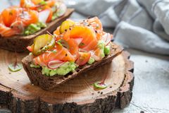 Smorrebrod with salmon on rye bread with vegetables and herbs. Danish open sandwich Smorrebrod with salmon on rye bread with vegetables and herbs Royalty Free Stock Photo