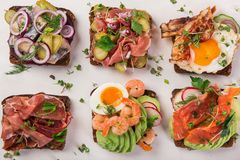 Smorrebrod, traditional Danish open sanwiches, dark rye bread wi. Th different topping,  top view Stock Photo