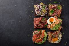 Smorrebrod, traditional Danish open sanwiches, dark rye bread wi. Th different topping, black background, top view, copy space Stock Photos
