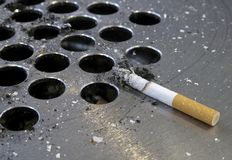 Smouldering cigarette. On a steel ash-tray Royalty Free Stock Photography