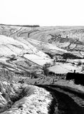 Smow scene with small country road in yorkshire moor. Landscape going downhill with fields and stone walls stock photo