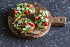Smörgåsar med jordgubbar, arugula och ädelost Läckert mellanmål, frukost eller ett mellanmål med vin Royaltyfria Foton